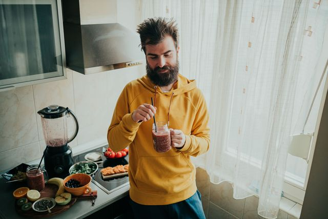handsome bearded man drinking healthy smoothie from a jar in the kitchen for breakfast