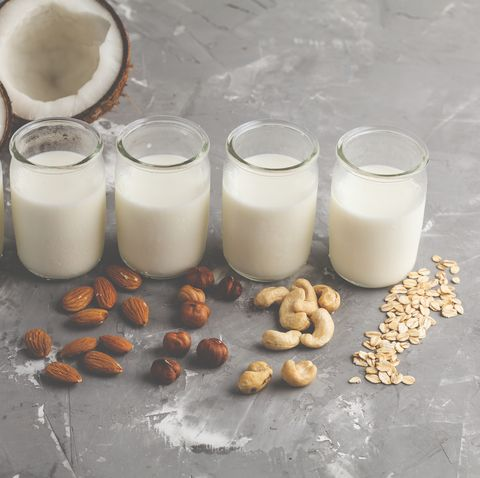 Vegan alternative nut milk in glass bottles on gray background. Healthy vegan food concept.