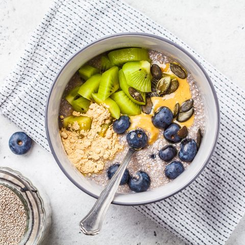 vegan breakfast chia pudding with kiwi, blueberries and peanut butter, top view