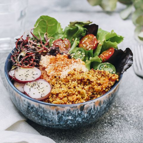 Vegan buddha bowl with hummus, quinoa with curry, lettuce, sprouts, green and red cherry tomatoes, sliced radish and sesame and poppy seeds
