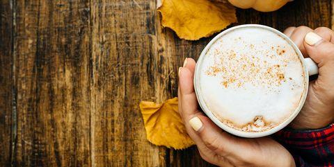 Vrouw vouwt handen om mok met pumpkin spice latte. Herfstbladeren en pompoen op houten achtergrond.