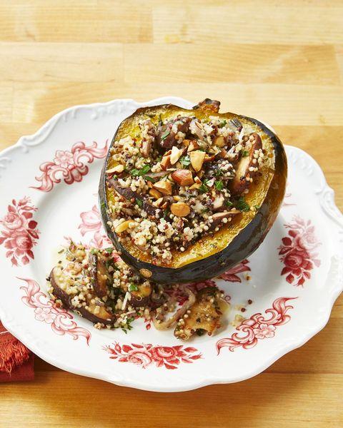 quinoa and mushroom stuffed acorn squash on white and red plate