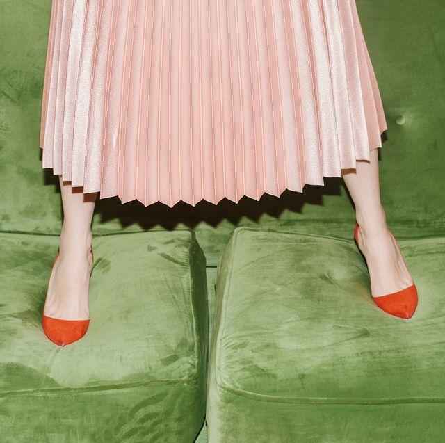 woman with pleated skirt standing on green velvet sofa
