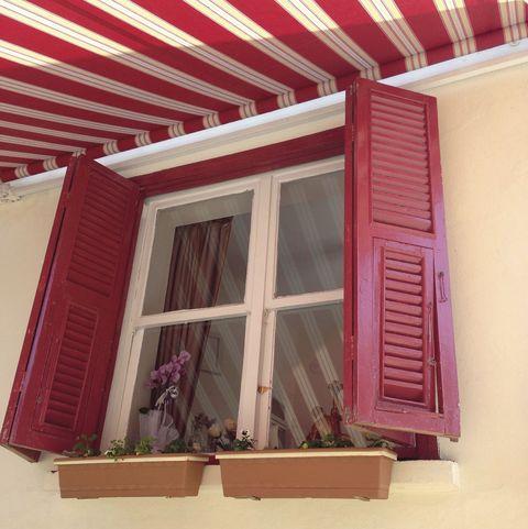 ventana roja con toldo a rayas rojas