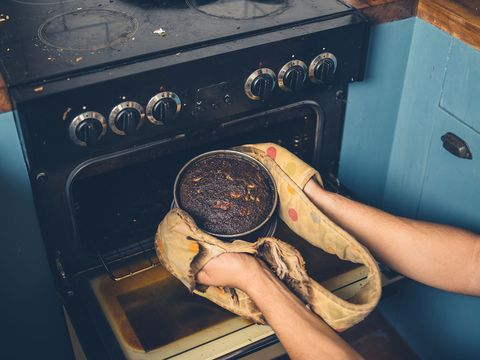 man haalt verbrande cake uit de oven