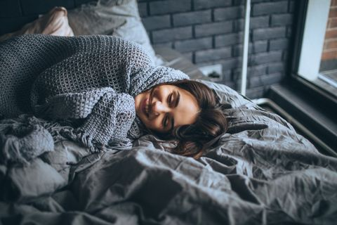 young woman in a bedroom, waking up
