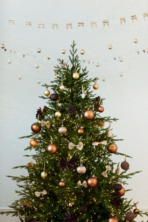 vertical photo of festively decorated christmas tree with pastel brown balls and ornaments on white background