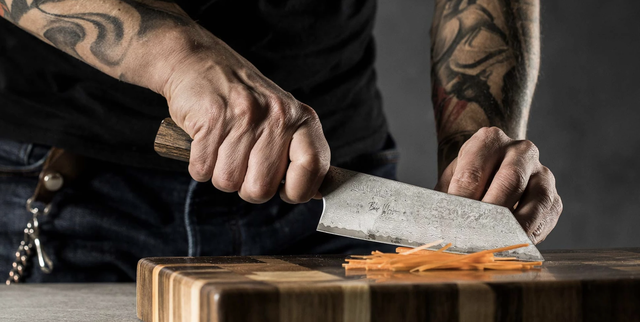 a man using a japanese knife to cut vegetables on a cutting board