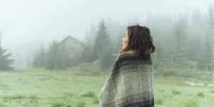 woman in a blanket looking at the fog