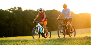 very happy smiling fit sporty couple on e mountain bikes on sunny afternoon in grassland