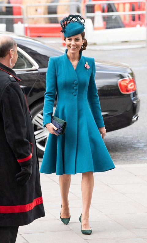 kate middleton en la calle con un vestido abrigo de color azul y un bolso de mano