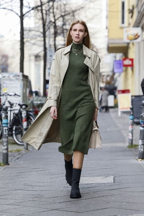 berlin, germany   december 15 model and plumber sandra hunke wearing a long army green knitted dress by zara, a beige trenchcoat by mango, a cream colored leather labyrinth bag with leopard head detail by marc cain and black boots by evenodd during a street style shooting on december 15, 2020 in berlin, germany photo by streetstyleshootersgetty images