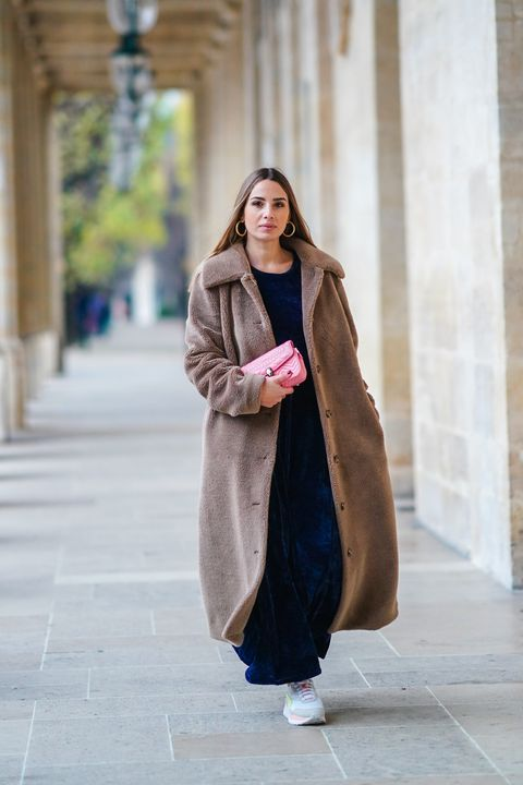 paris, france   december 07 maria rosaria rizzo wears raspini golden jewelry, a blue velvet long dress from cheyma, a pink bulgari bag, a brown fluffy wool long teddy winter coat from song of style, puma sneakers shoes,  on december 07, 2020 in paris, france photo by edward berthelotgetty images