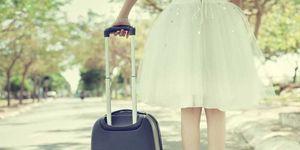 Una donna di spalle con un trolley