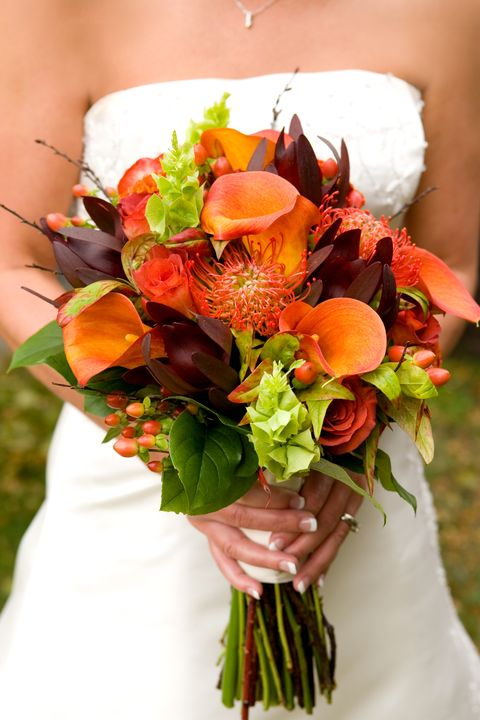 female bride holding a bouquet of beautiful fall colored flowers ready to walk down the aisle flowers are in focus