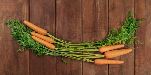 vibrant organic orange carrots with leafy greens, shot from the top on a dark rustic wooden background with copy space
