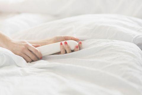 Vrouw houdt vibrator vast in bed