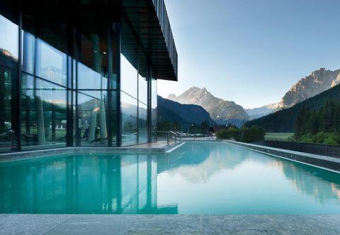 Swimming pool, Property, Reflection, Glass, Mountain range, Real estate, Aqua, Azure, Resort, Composite material,
