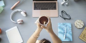 View from above businesswoman drinking tea at desk