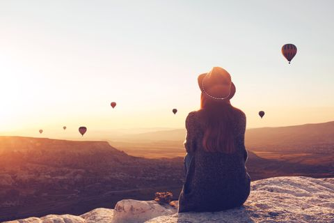 View from the back of a girl in a hat sits on a hill and looks at air balloons.