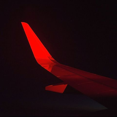 View of a airplane wing at night during a red eye flight