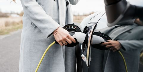 view of woman's hand plugging in charging lead to her electric car