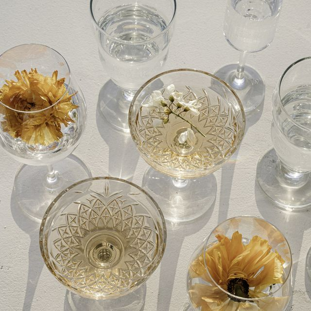 still life photography close up of wineglasses with orange flowers in it and rose wine in sunset sun light
