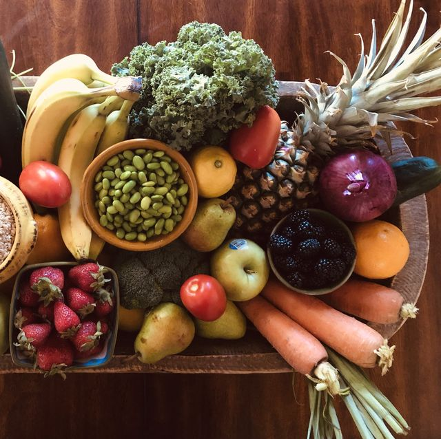 a vintage dough bowl is filled with fresh organic fruits and vegetables