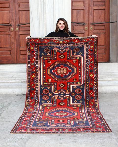woman holding up vintage rug