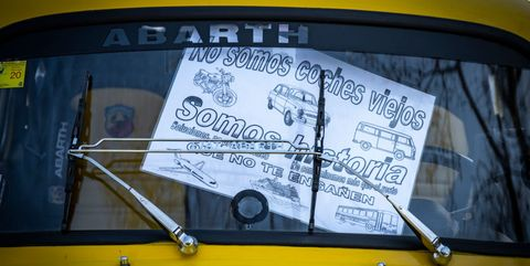 A vintage vehicle parked with a placard against the Low...