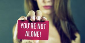 Young woman holding you're not alone card
