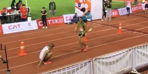 runner helps exhausted competitor across line