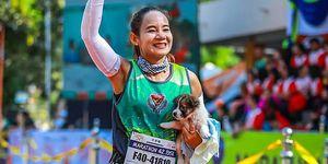 woman runs marathon holding puppy