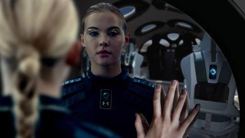 一個女生在 virgin galactic 太空梭的小圓鏡看自己