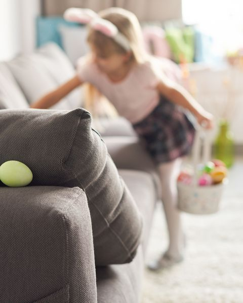 girl searching for easter eggs on sofa