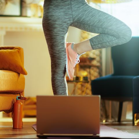 long distance valentines day   closeup on fit sports woman in sport clothes in the modern house using online personal fitness trainer service in laptop and stretching