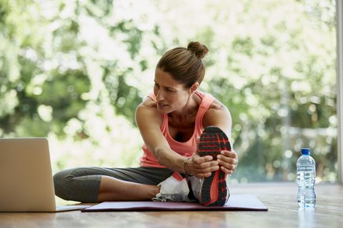 Woman looking at laptop while exercising at gym