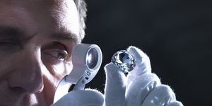 Jeweller inspecting replica diamonds with loupe