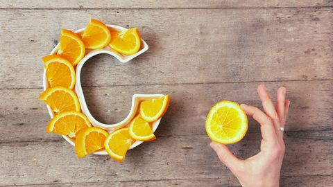 vitamin c or ascorbic acid nutrient in food concept plate in shape of letter c with orange slices and woman's hand with citrus making sign ok on wooden background flat lay or top view