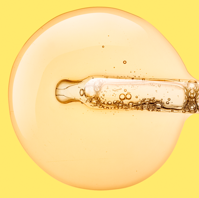 oil coming from pipette on yellow background