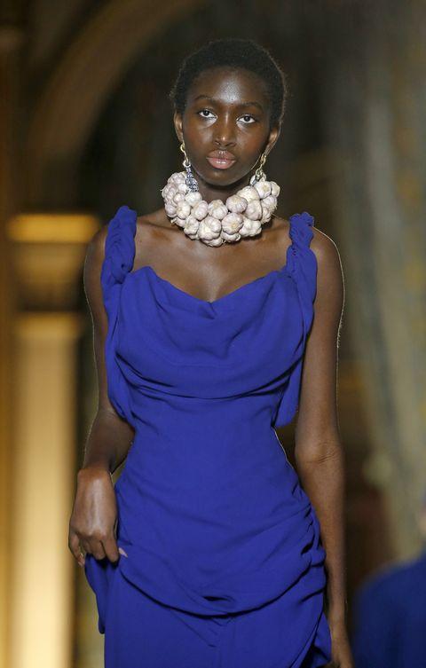 Beeld van de Vivienne Westwood show in Parijs, model draagt ketting van knoflooktenen