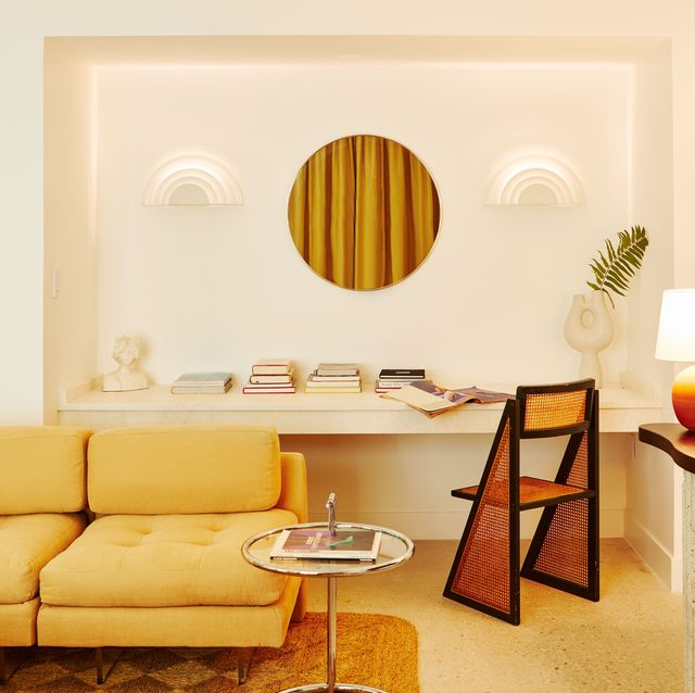 interior shot of living space with couch, rattan chair, lamp, and books on a counter space