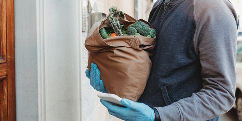 a volunteer is delivering a bag of vegetables and fruit