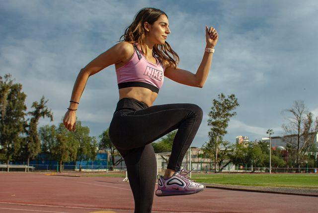 vrouw doet oefeningen op atletiekbaan