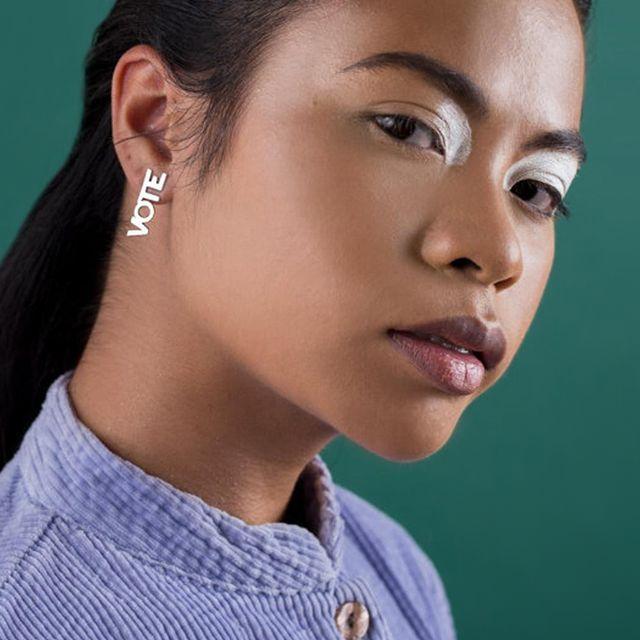 """model wearing silver """"vote"""" earrings"""