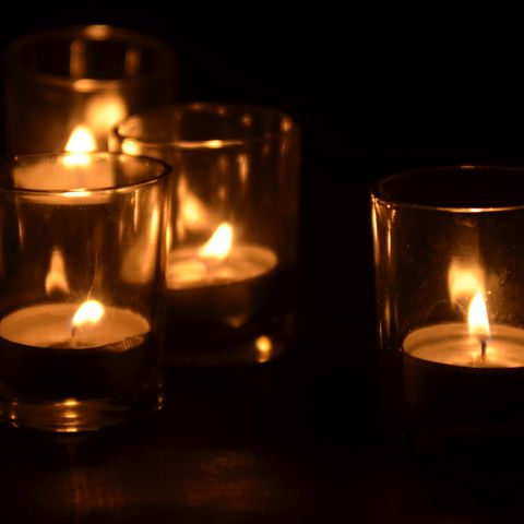 4 votive candles inside glass containers