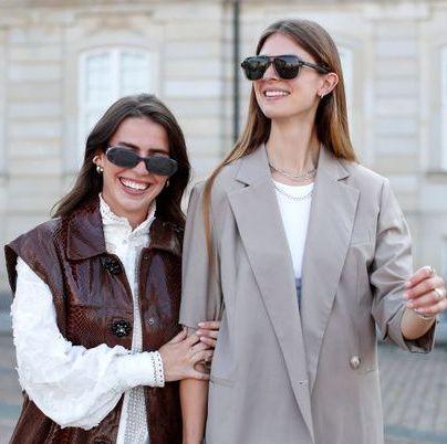 twee vrouwen met zonnebrillen, een in grijze blazer en een in witte blouse met jack met korte mouwen buiten op een plein