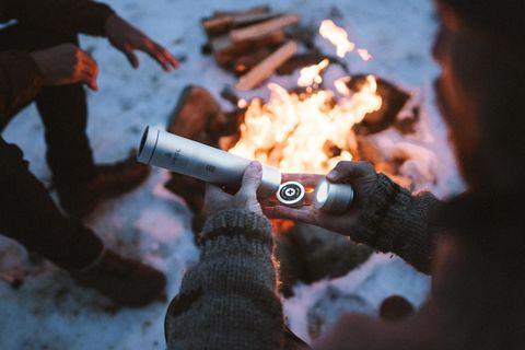 a man opening a metal cylinder near a campfire