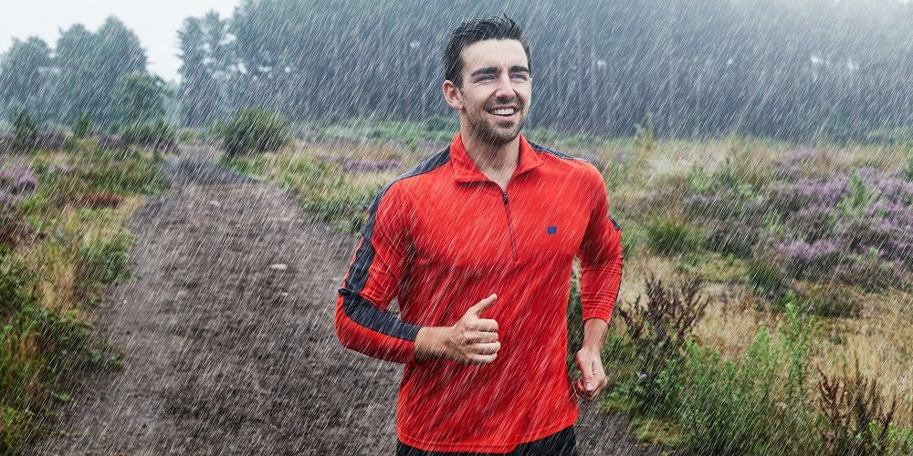 Jogger running on path in rain.