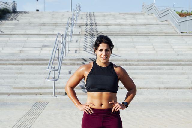 sportieve vrouw staat met handen in zij voor trap